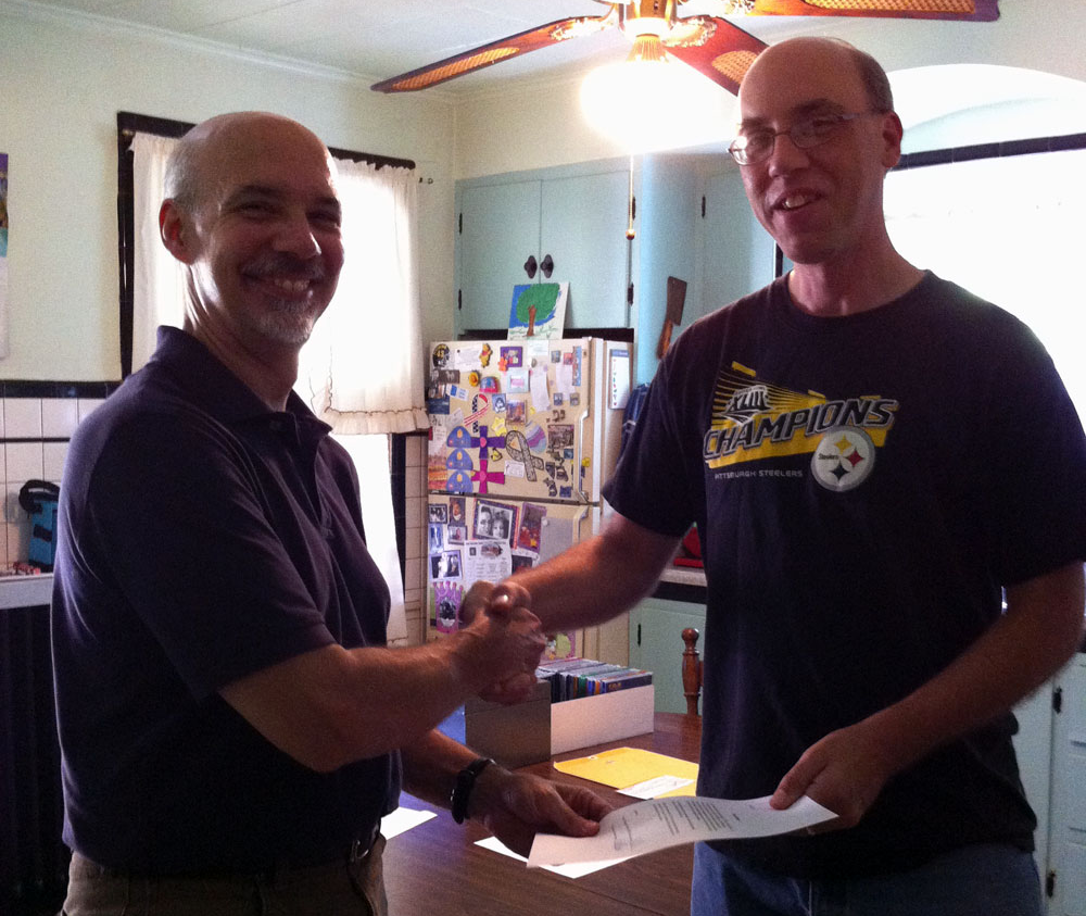 Coddington, left, and Neville shake hands after signing the purchase agreement on August 10, 2013, at Neville's home outside Pittsburgh, Pa.